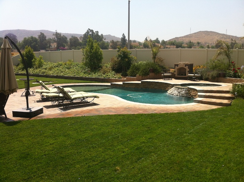 Freeform Landscaped Pool And Spa With Raised Patio And Fireplace